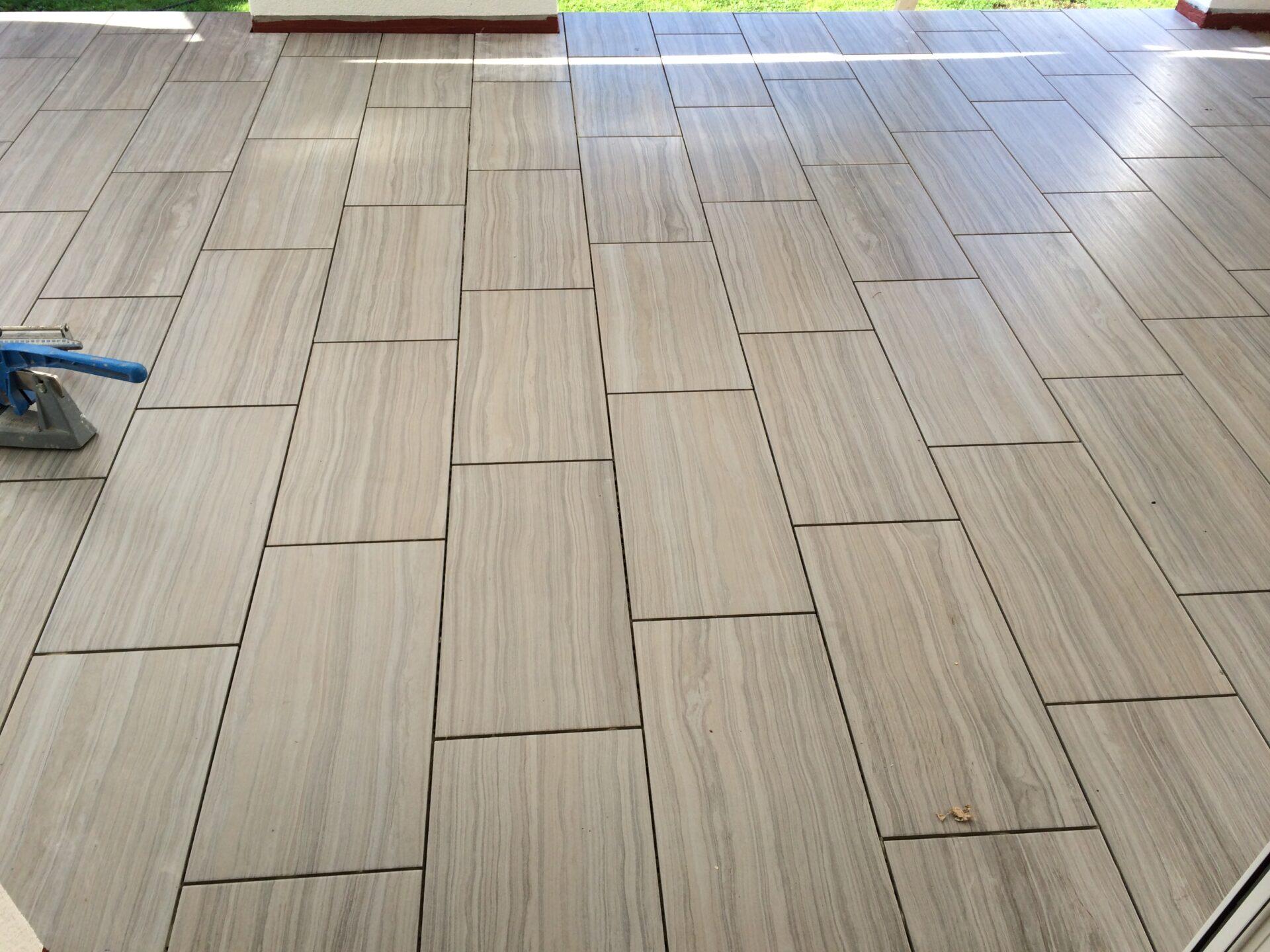 Polaganje talnih ploščic na teraso v temno rjavi barvi fug